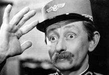 Herec Vlasta Burian salutuje v železničnej čiapke.